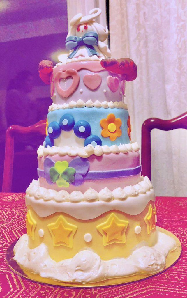 la torta di Alcremie con gli ultimi dettagli: nuvolette e filtro viola